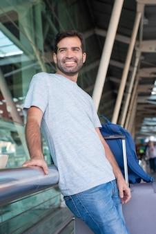 空港で金属の手すりにもたれて笑顔の若い男