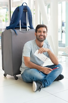 荷物の近くに座っている若い男の笑みを浮かべてください。