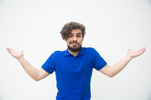 Беззаботный невежественный парень пожимает плечами и разводит руками