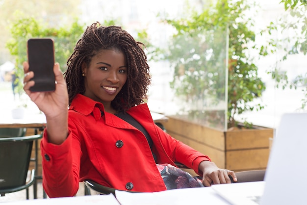 空白の画面を持つスマートフォンを示す陽気な女性