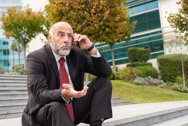 Смущенный зрелый бизнес-лидер, говорящий по сотовому