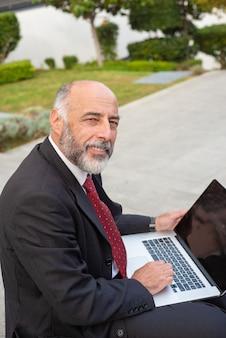Довольный бизнесмен используя компьтер-книжку и смотря