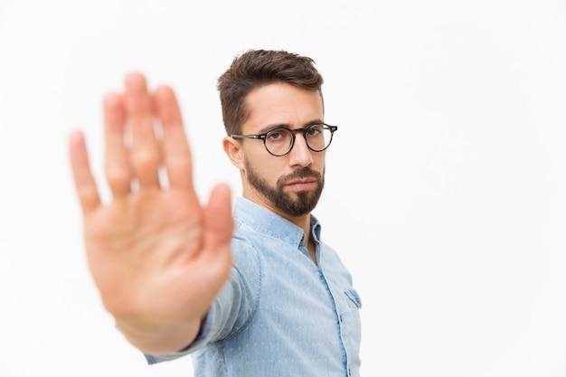 Серьезный строгий парень делает жест рукой стоп