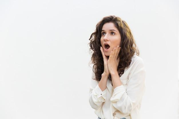 Шокированная взволнованная женщина задыхается, трогая щеки