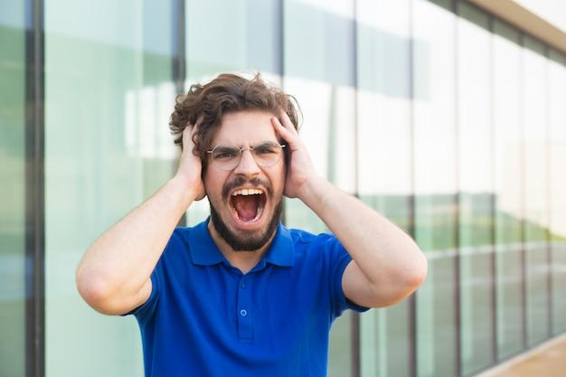 Шокированный парень держит голову, громко крича