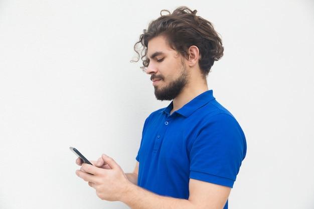 Сторона сфокусированного парня отправляя смс сообщение на смартфоне