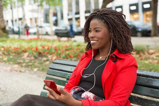 Улыбается женщина в наушниках с помощью смартфона