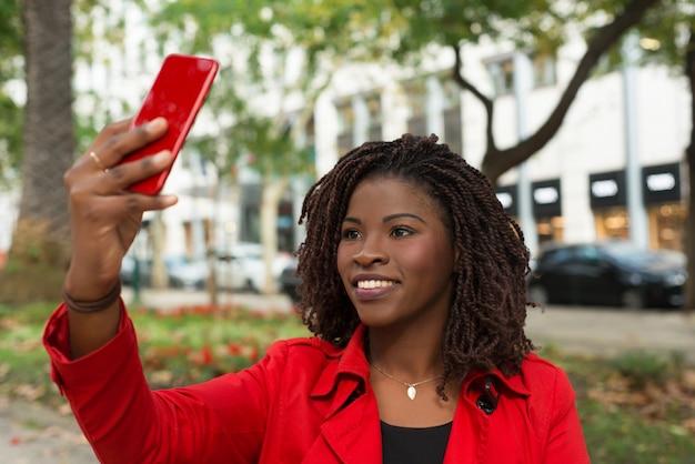 Улыбается женщина, принимая селфи с смартфон на открытом воздухе