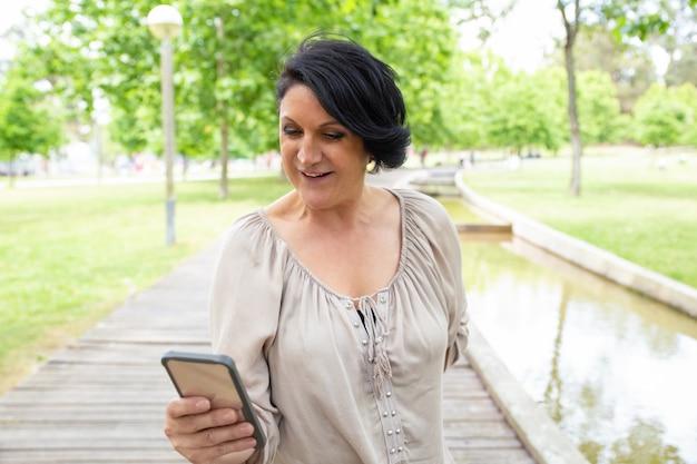 Улыбается женщина, используя смартфон на открытом воздухе