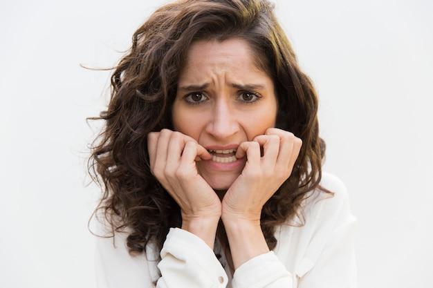 Расстроенная нервная женщина кусает ногти
