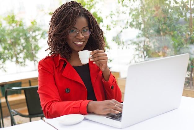Женщина пьет кофе и с помощью ноутбука