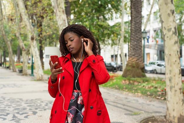公園で携帯電話を介して音楽を聴く女性