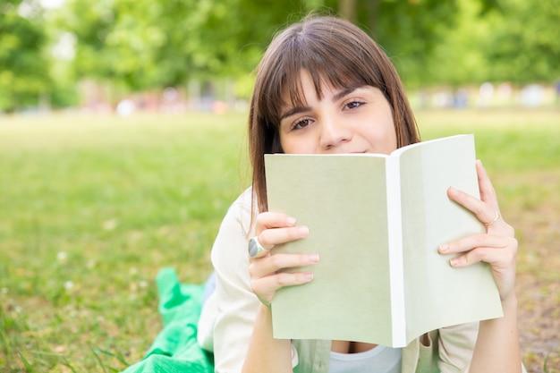 Книга чтения молодой женщины в парке