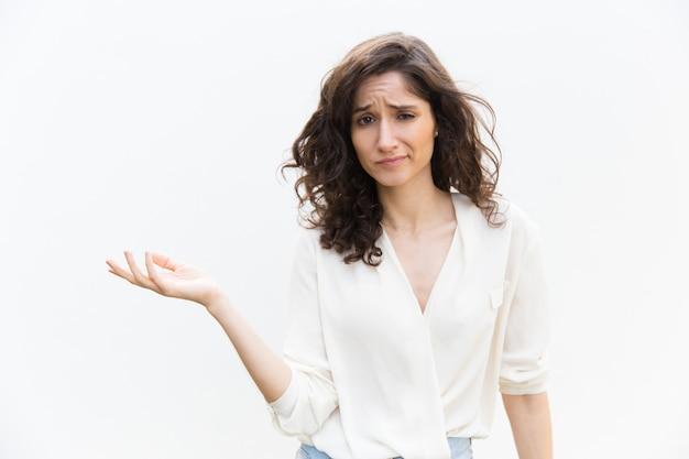Сомнительная женщина указывая рукой на пустой копией пространства