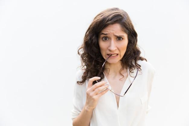 Смущенная подчеркнутая женщина кусает очки храма