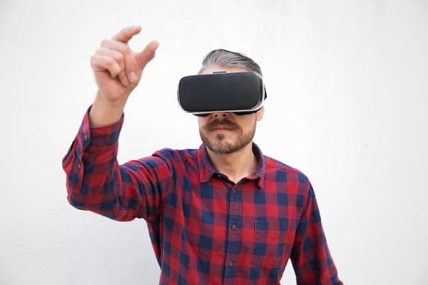仮想現実のヘッドセットで焦点を当てたひげを生やした男