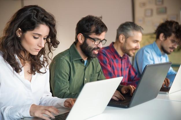 Сосредоточенные коллеги, использующие ноутбуки за столом встречи