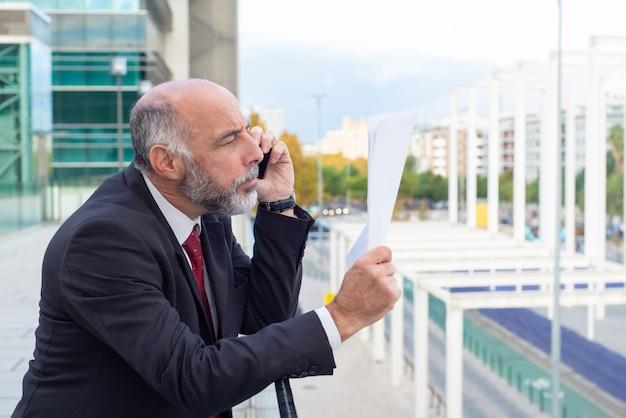 Сосредоточенный зрелый бизнесмен, читающий документ