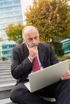 Сосредоточенный зрелый бизнесмен, используя ноутбук на открытом воздухе