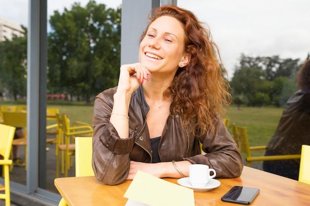 屋外のコーヒーショップで朝を楽しんで幸せな屈託のない女性