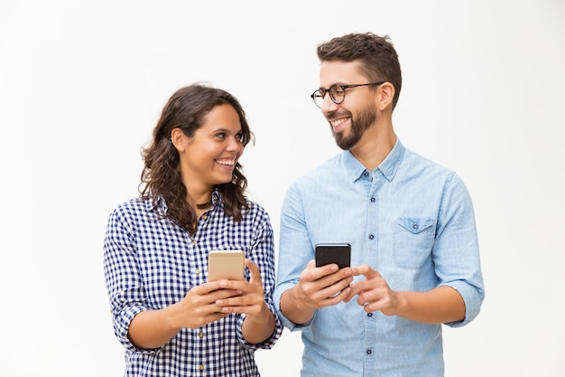 Счастливая веселая пара с мобильными телефонами в чате