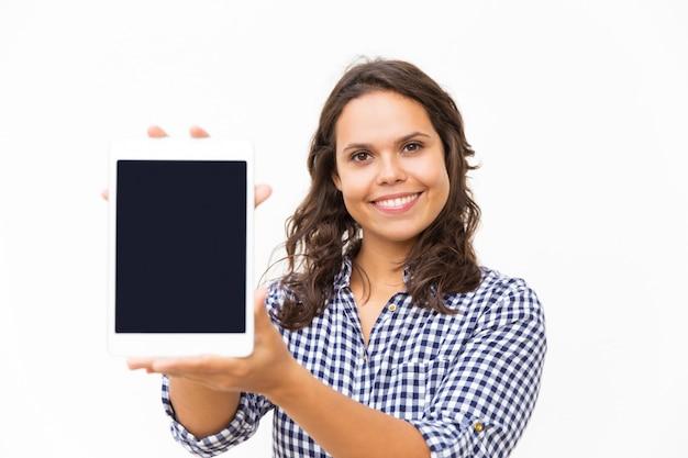 新しいインターネットアプリを提示する幸せなうれしそうなタブレットユーザー