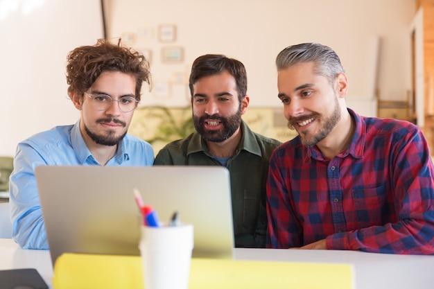 Счастливая команда стартапа наблюдает за презентацией на мониторе