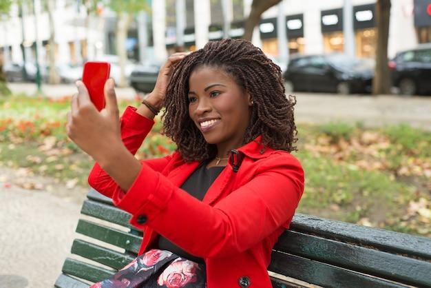 Счастливая женщина, используя смартфон в парке