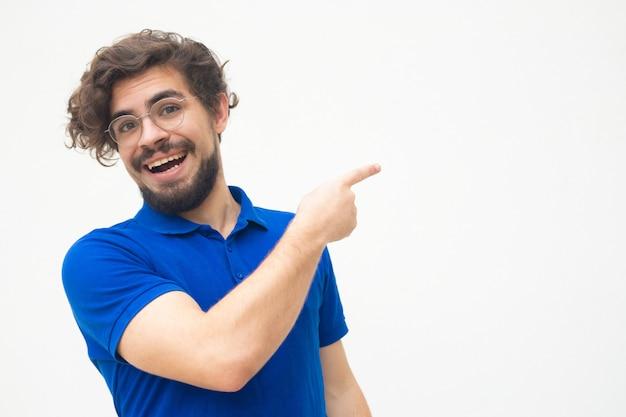 Радостный позитивный парень, указывая пальцем