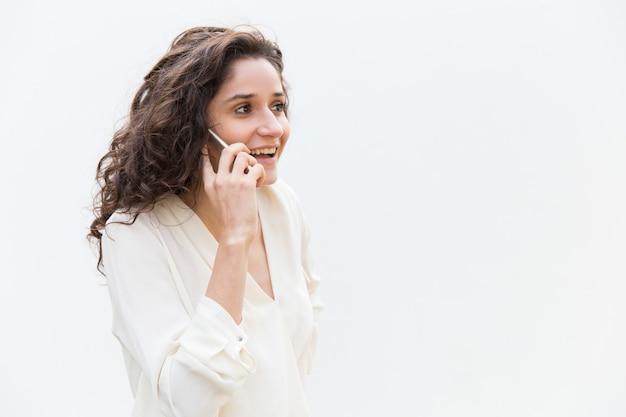 携帯電話で話しているうれしそうな肯定的な女性