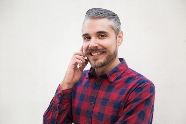 Радостный довольный мужчина разговаривает по мобильному