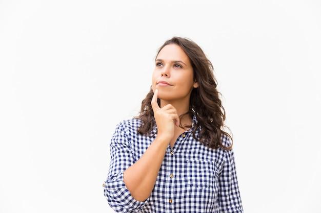 Задумчивая женщина касается подбородка и смотрит в сторону