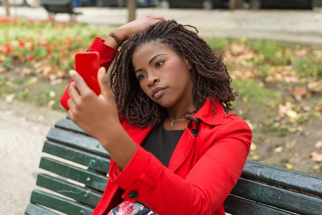 Мечтательная женщина, используя смартфон в парке