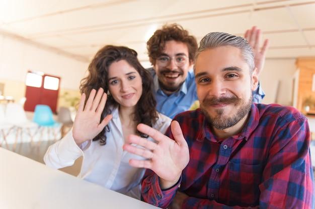 Портрет счастливой успешной творческой команды машет привет