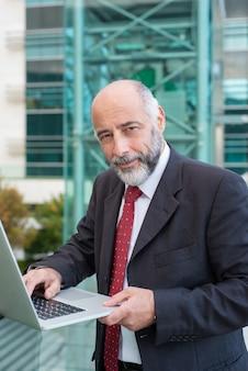 Положительный уверенно серый с волосами бизнесмен, используя ноутбук