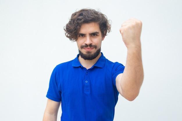 Положительный уверенный парень показывает кулак