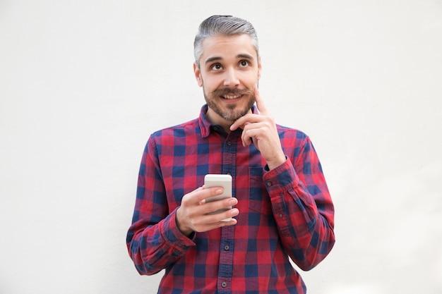 Позитивный задумчивый пользователь мобильного телефона, почесывая бороду