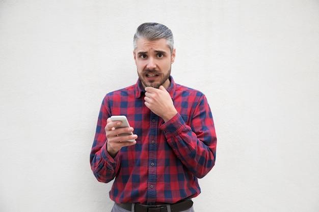 怖がっている中年の男がスマートフォンを保持