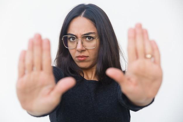 停止ジェスチャーを作る動揺して怖い女性