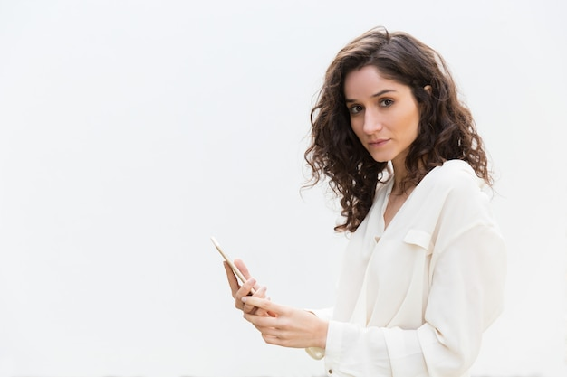 探しているスマートフォンで深刻な美しい女性