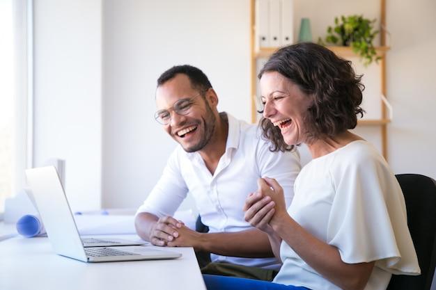 Веселые сотрудники смотрят на ноутбук и смеются
