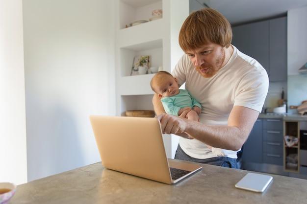 赤ちゃんの娘を保持している陽気な新しいお父さん