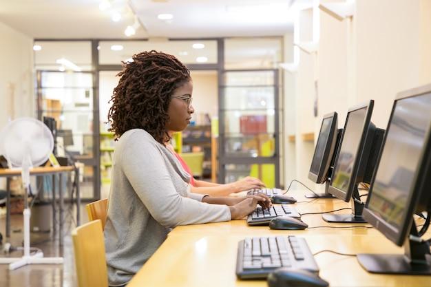 Сосредоточена женщина, набрав на клавиатуре компьютера