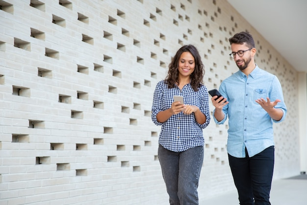 歩いて笑顔のカップルとスマートフォンを使用して