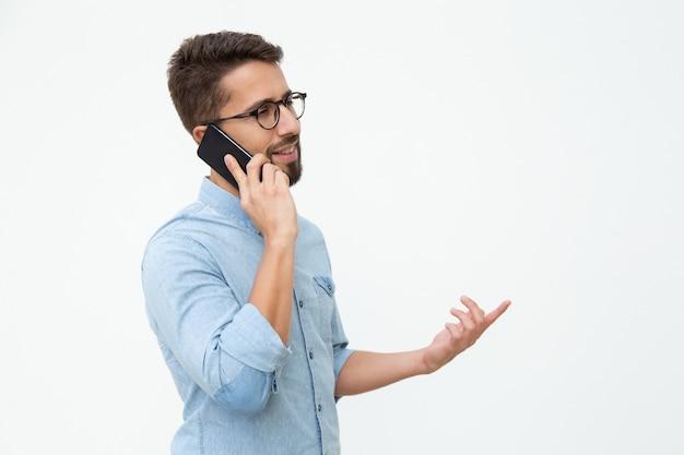 スマートフォンで話している若い男の笑みを浮かべてください。