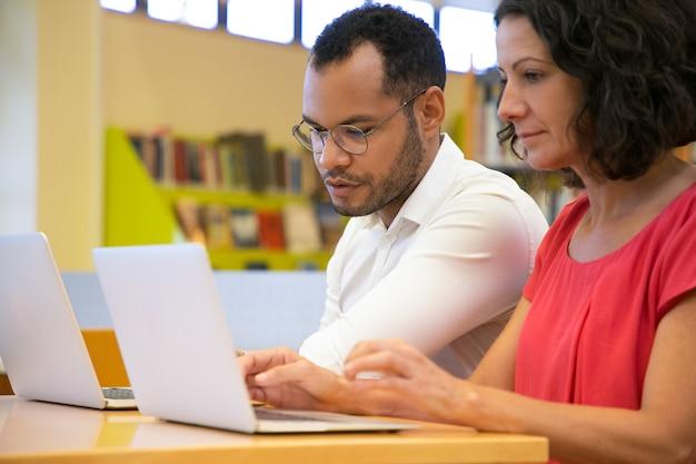 Два концентрированных студентов говорят и смотрят на ноутбук в библиотеке
