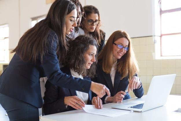 Концентрированные деловые женщины работают с ноутбуком