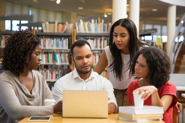 Сконцентрированные молодые люди читают информацию с ноутбука