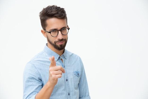 Уверенный в себе молодой человек, указывая на камеру