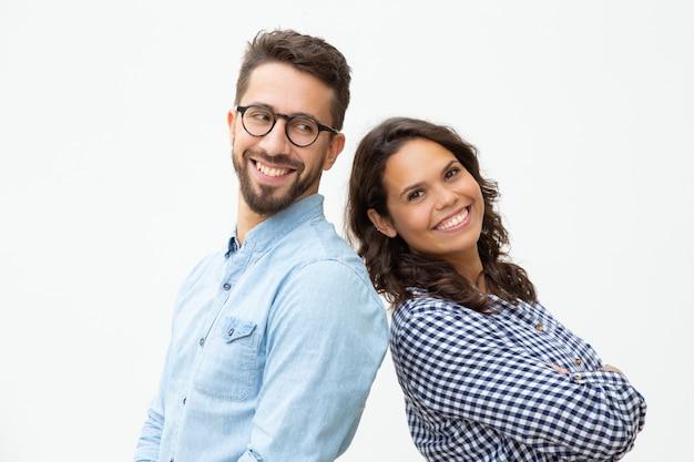 Довольный мужчина и женщина, стоящие спиной к спине